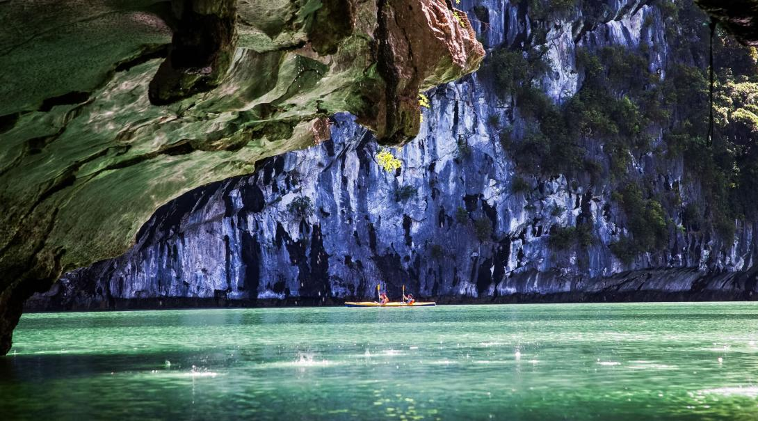 Travellers kayak among the islands in Ha Long Bay, Vietnam.